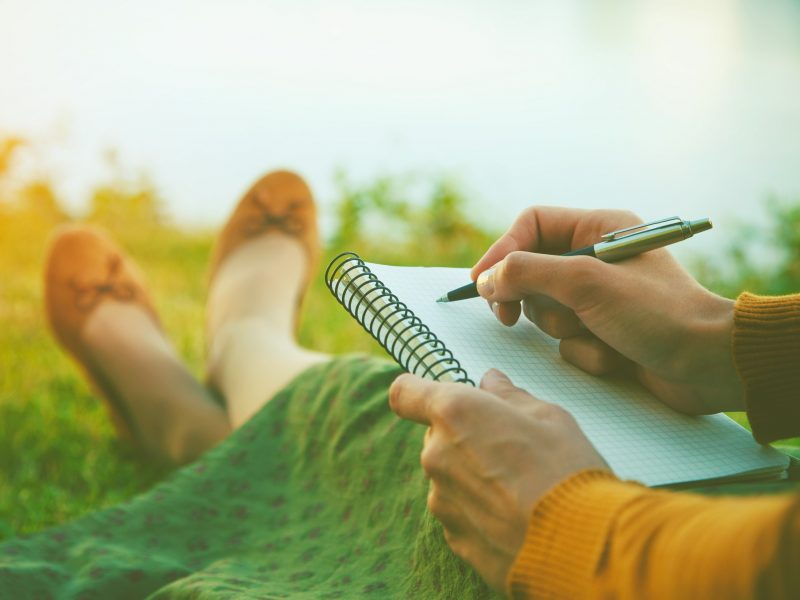 Woman sitting on grass journaling